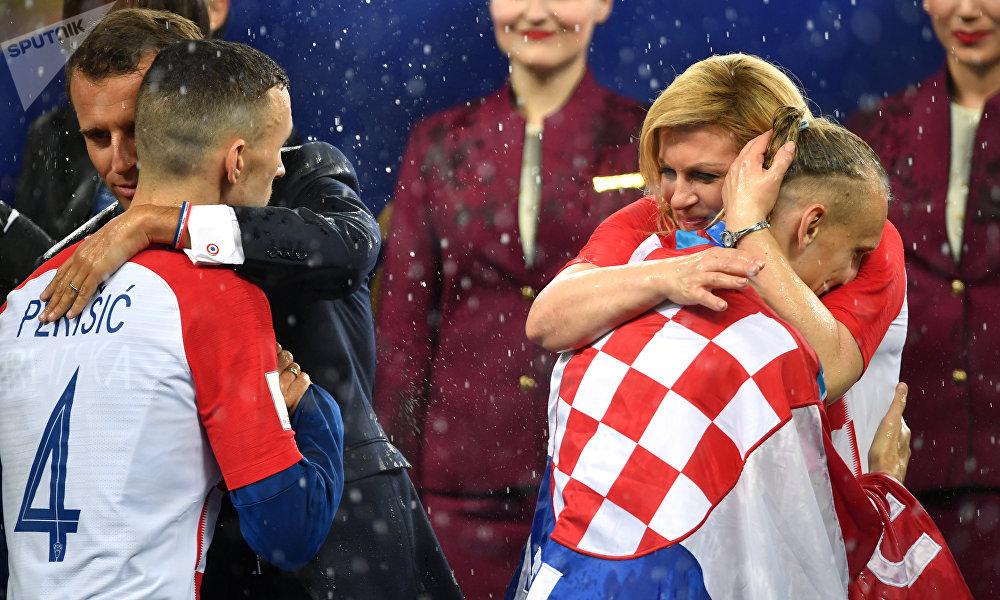 Presidentes de França e Croácia, Emmanuel Macron e Kolinda Grabar Kitarovic, abraçam jogadores croatas após final da Copa do Mundo