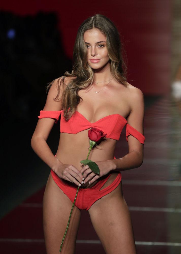 Modelo posa com rosa na passarela, apresentando um novo biquíni sensual