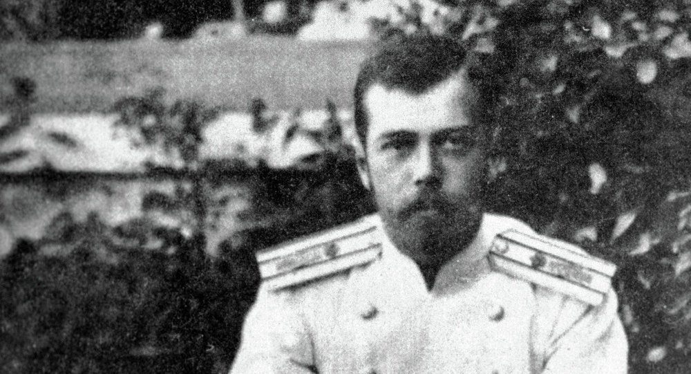 Emperor Nicholas II stands leaning against a straw armchair