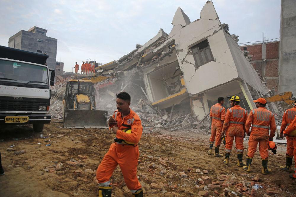 Equipe de resgate trabalhando no lugar onde colapsou um prédio, Índia.