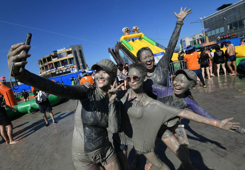 Turistas tirando selfie durante o Festival de Lama de Boryeong, Coreia do Sul.