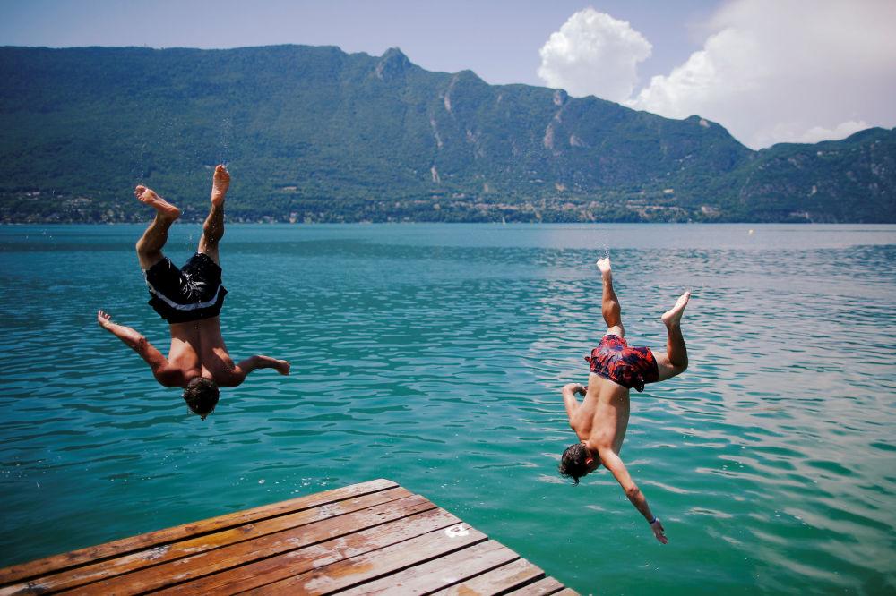 Rapazes saltando para o lago Bourget, França.