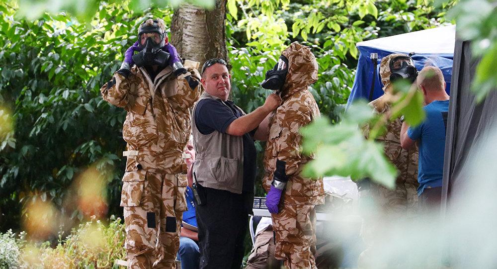 Investigadores vestem trajes militares de proteção contra materiais perigosos durante uma busca policial em Salisbury, Inglaterra.