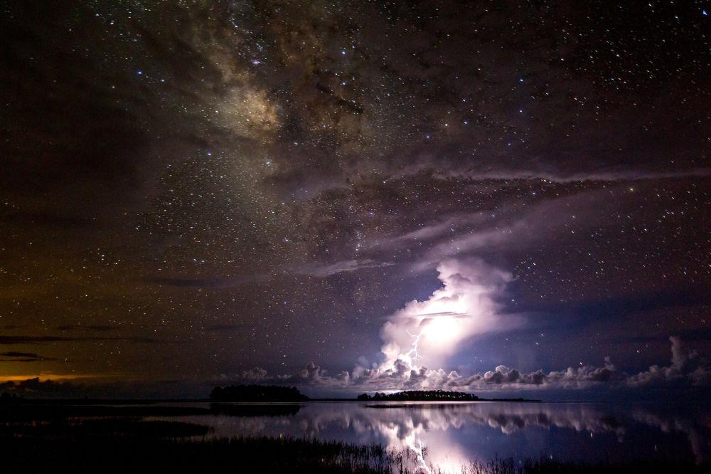 Tempestade sob a Via Láctea por Tianyuan Xiao. Nossa galáxia gloriosa paira sobre uma tempestade que ilumina o céu da Flórida. O fotógrafo mostra o excelente contraste entre os objetos estáveis (Via Láctea) e móveis (tempestade) no céu