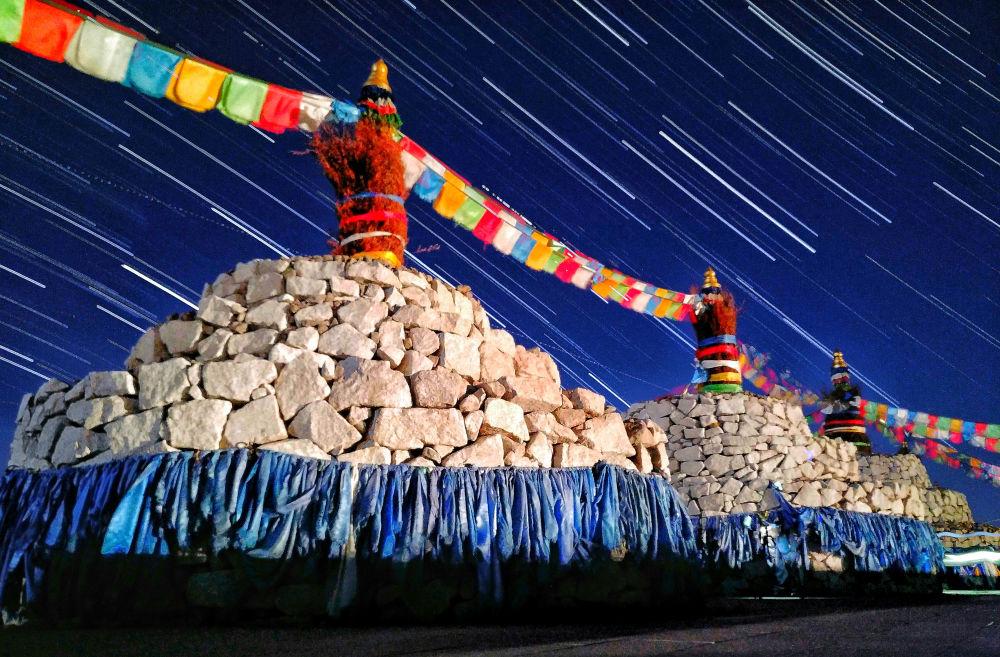 Estrelas sobre o sagrado mongol Ovoo – pedra sagrada da Mongólia por Qiqige Zhao. A imagem, tirada em uma noite de verão em Mingantu, mostra rastros das estrelas cadentes sobre os altares sagrados