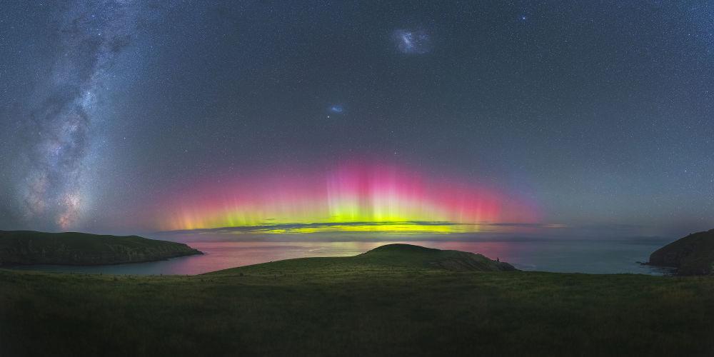 Empírico por Paul Wilson. Águas de Southern Bays (Nova Zelândia) refletem as cores brilhantes rosa e amarela lançadas pela Aurora iluminada. A tonalidade escura de amplos campos verdes e o céu azul-escuro são sombreados por incríveis cores vivas da aurora