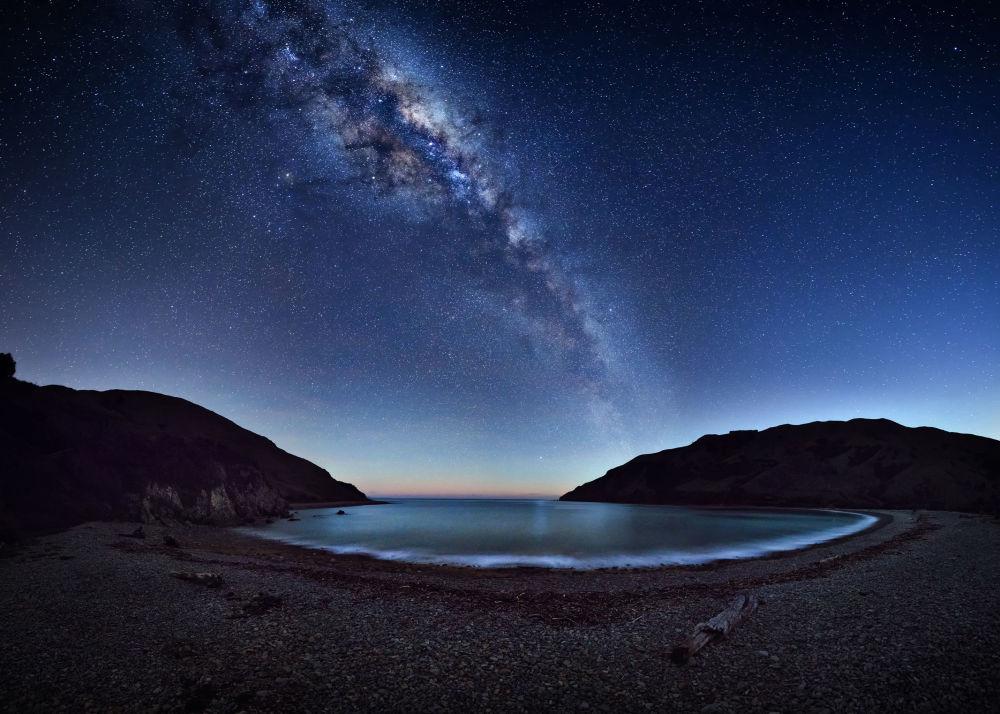 Cable Bay por Mark Gee. A encantada Via Láctea estende-se pelo céu noturno e é refletida por Cable Bay (Nova Zelândia). Para criar essa imagem panorâmica, o fotógrafo precisou de 42 fotos separadas