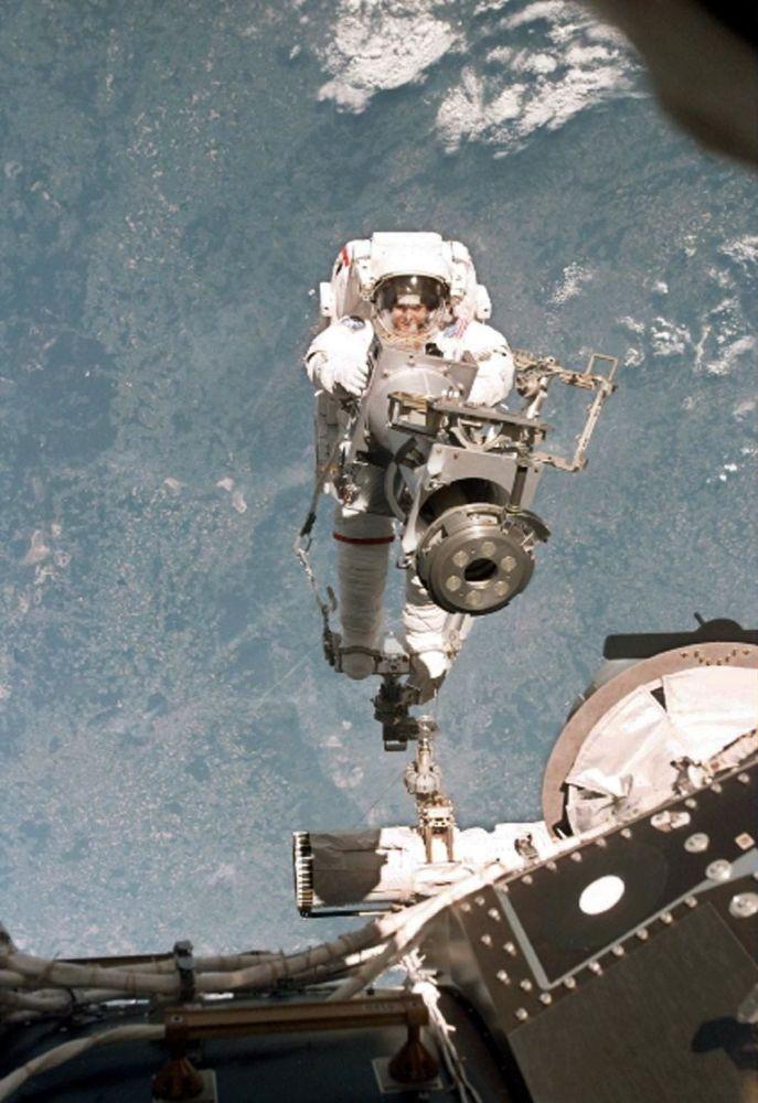 A vista do ônibus espacial Discovery mostra a astronauta norte-americana Tamara Jernigan, enquanto ela dirige o braço robótico do ônibus espacial até a Estação Espacial Internacional, em 30 de maio de 1999