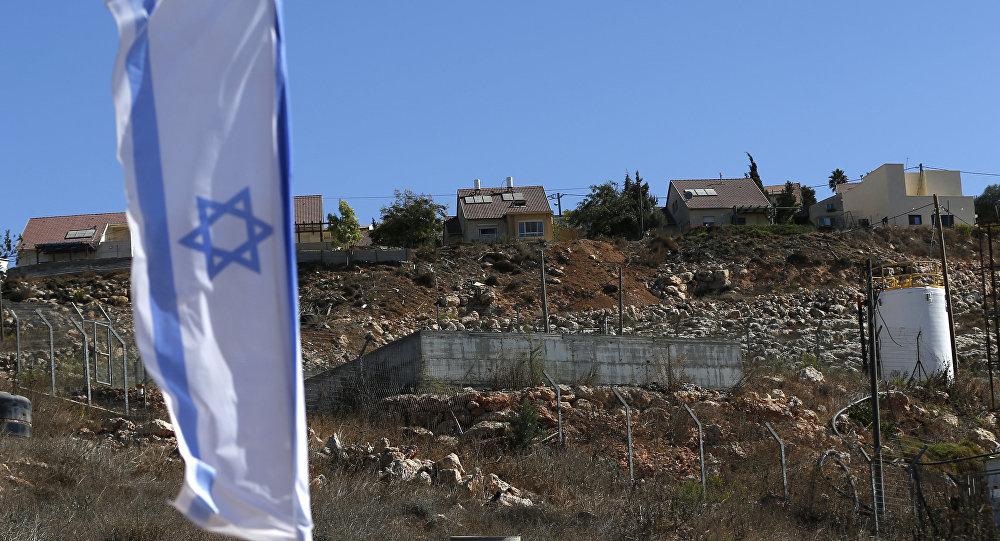 Bandeira nacional israelense que voa ao lado de um local de edifício israelita de unidades de alojamento novas no estabelecimento judaico de Shilo na Cisjordânia palestina ocupada.