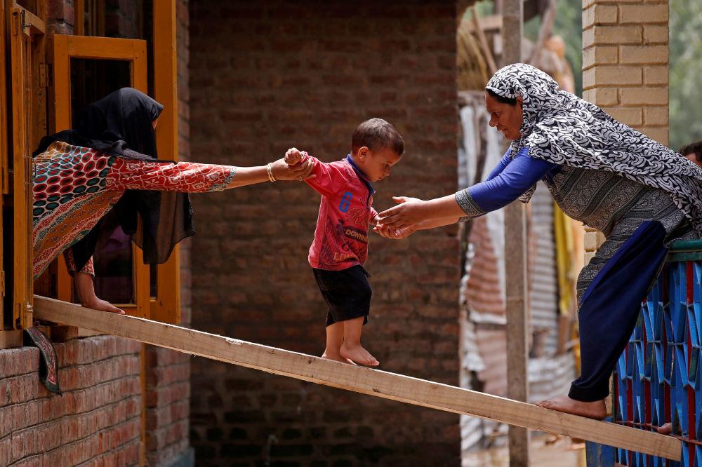 Mulheres ajudando uma criança a passar para outra casa por uma tábua de madeira após inundações nos arredores de Srinagar, Jammu e Caxemira, Índia.