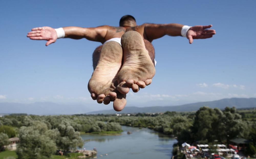 Vencedor da competição anual de saltos de ponte, Florid Gashi, pula da ponte Ura e Shenjte, na cidade de Gjakova, Kosovo.