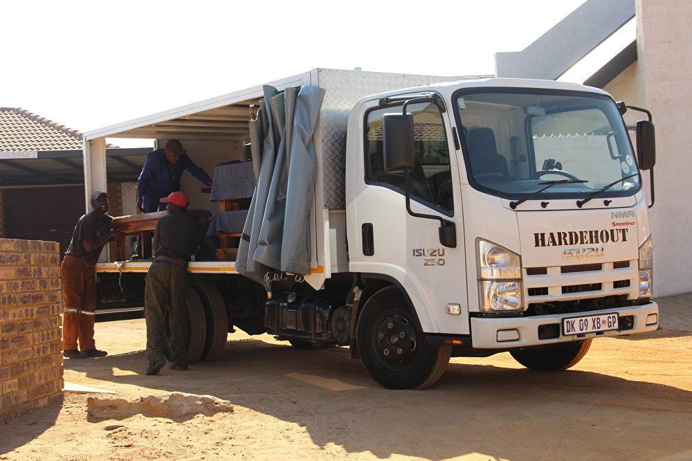 Negros descarrem um caminhão com produtos encomendados, em Kleinfontein