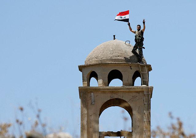 Militar sírio hasteia bandeira da Síria na praça central da cidade de Quneitra, 27 de julho de 2018
