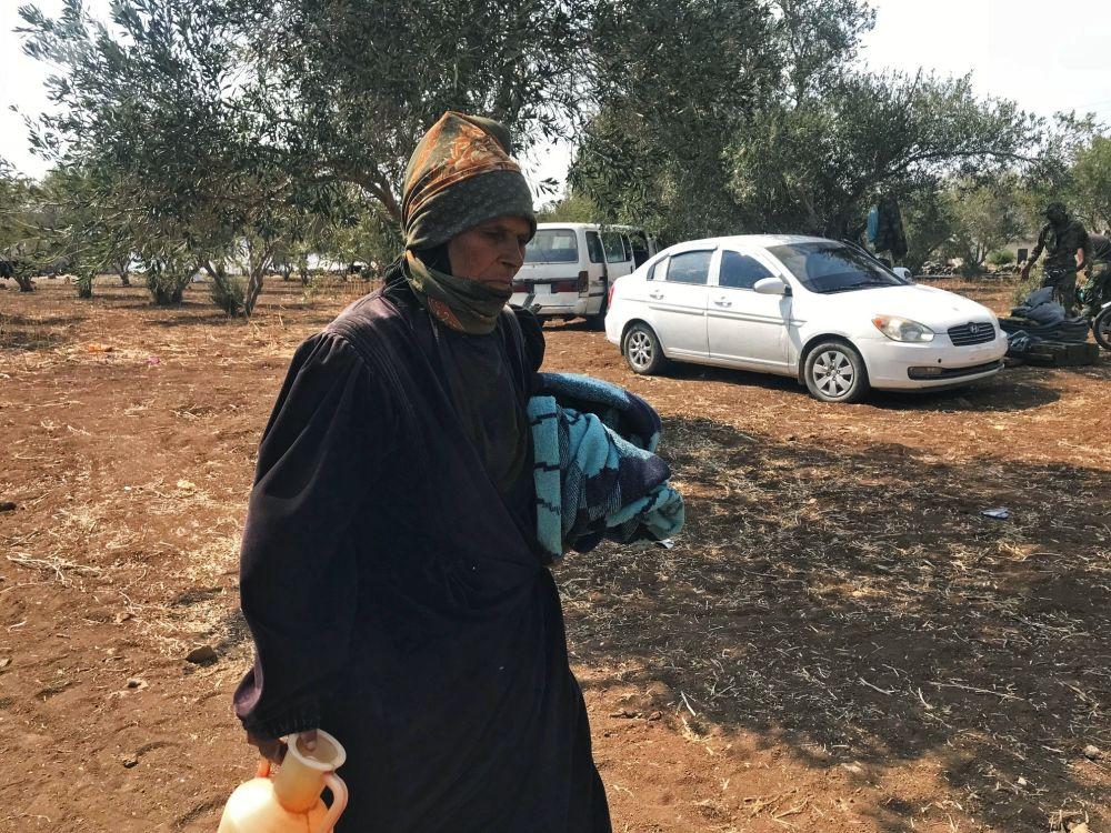 Mulher com jarro de água caminhando por Daraa