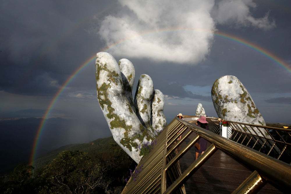 Arco-íris duplo aparece por cima da estrutura de mãos gigantes da Ponte Dourada em Ba Na Hills, na cidade vietnamita de Danang