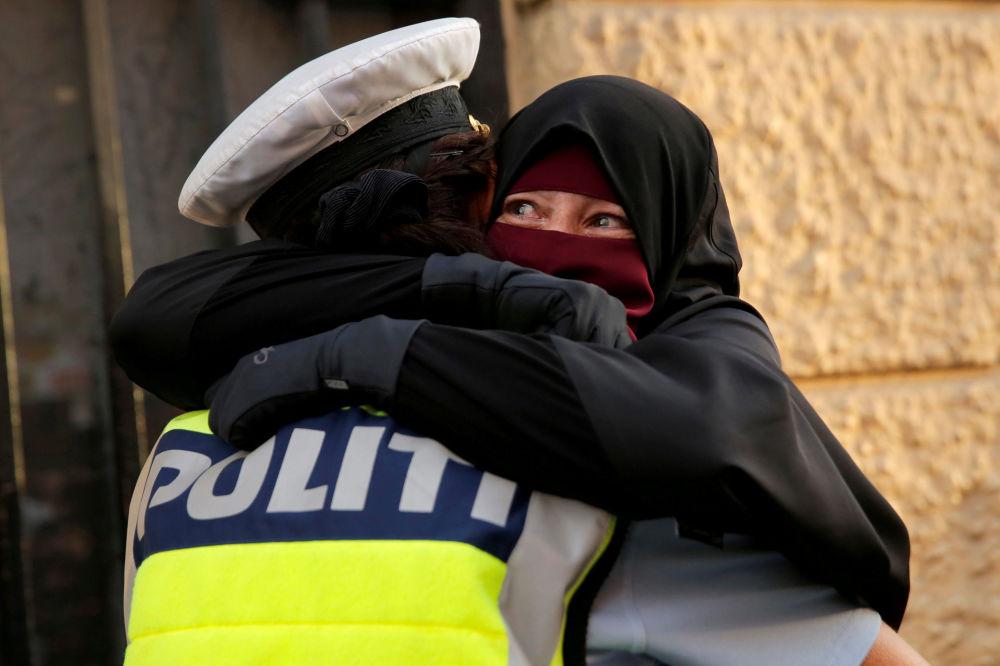 Mulher assustada abraça um policial durante uma manifestação contra a proibição do uso de niqab na rua, na Dinamarca