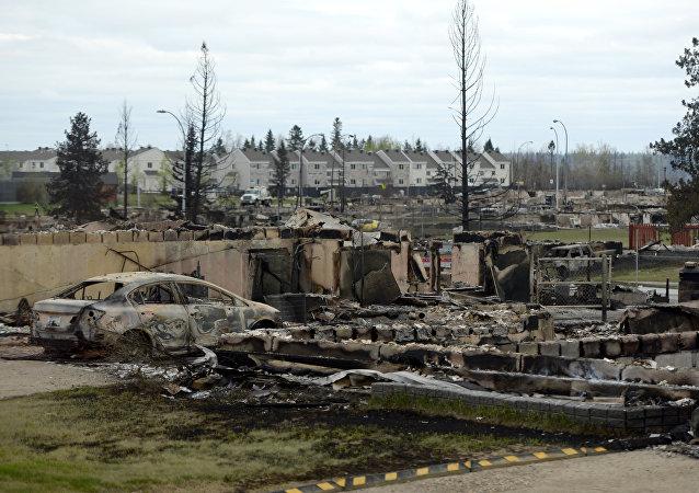 Carro queimado e restos de casa, Alberta, Canadá, 9 de maio de 2016 (imagem referencial)
