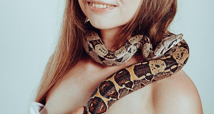 Mulher com cobra no pescoço