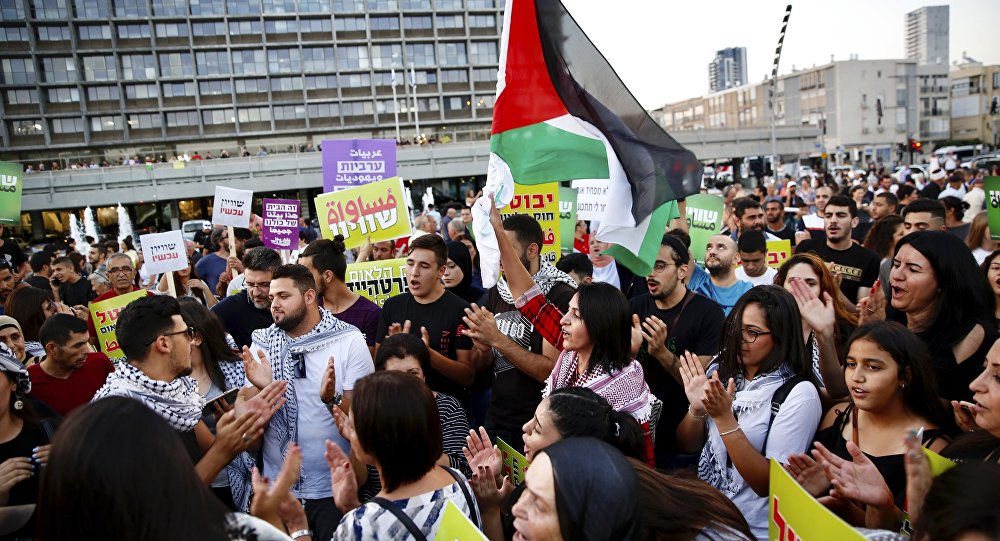 Árabes israelenses carregam bandeira da Palestina durante protesto contra a Lei do Estado Judeu, em Tel-Aviv.