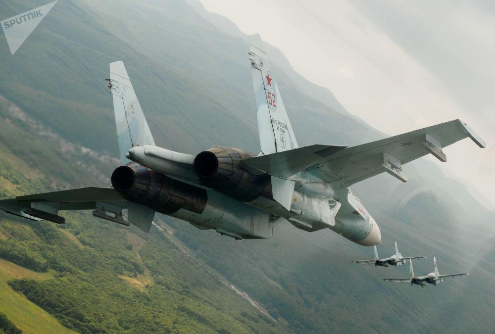 Caças polivalentes Su-27 durante voos de demonstração no Dia das Portas Abertas do regimento aéreo do Distrito Militar do Sul em comemoração do 105º aniversário da Força Aeroespacial da Rússia