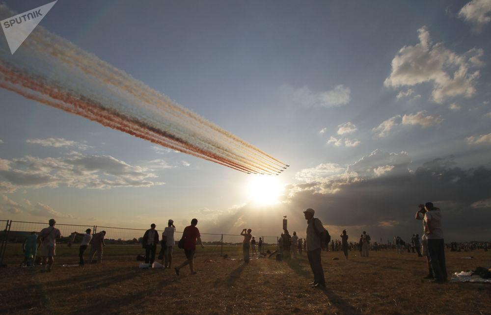 Espectadores assistindo ao voo de uma formação de aviões que desenham a bandeira russa no céu no aeródromo de Zhukovsky