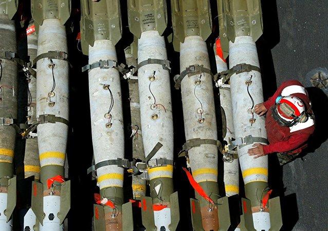 Manipulador de munição da Marinha dos EUA fica perto de bombas guiadas MK-82 no convés de voo do USS Kitty Hawk, nas águas do norte do Golfo, em 28 de março de 2003