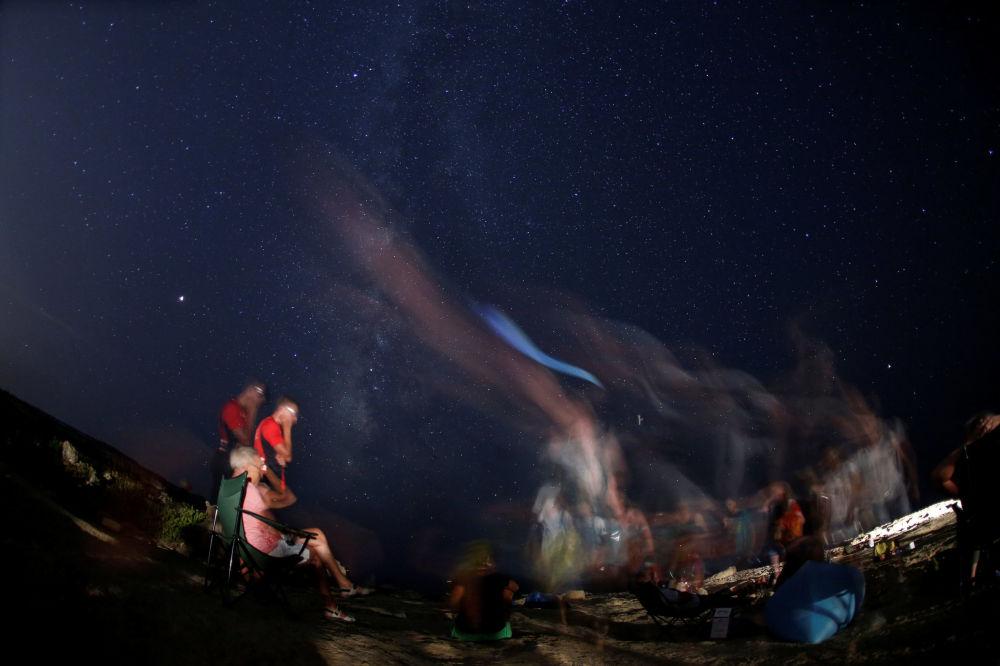 Pessoas observando a chuva de meteoros em praia rochosa de Malta