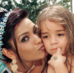 Miss Mundo 1997 e modelo indiana, Diana Hayden, beija uma criança um dia após sua vitória nas Seychelles