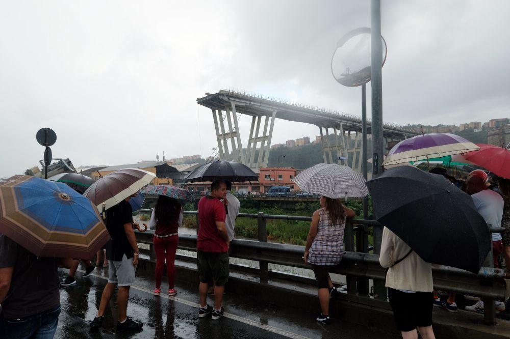 Pessoas observando a operação de resgate perto da ponte destruída