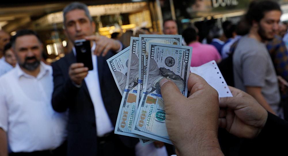 Um empresário segurando dólares EUA posa para seu amigo na frente de um escritório de troca de moeda em resposta à chamada do presidente turco Tayyip Erdogan.