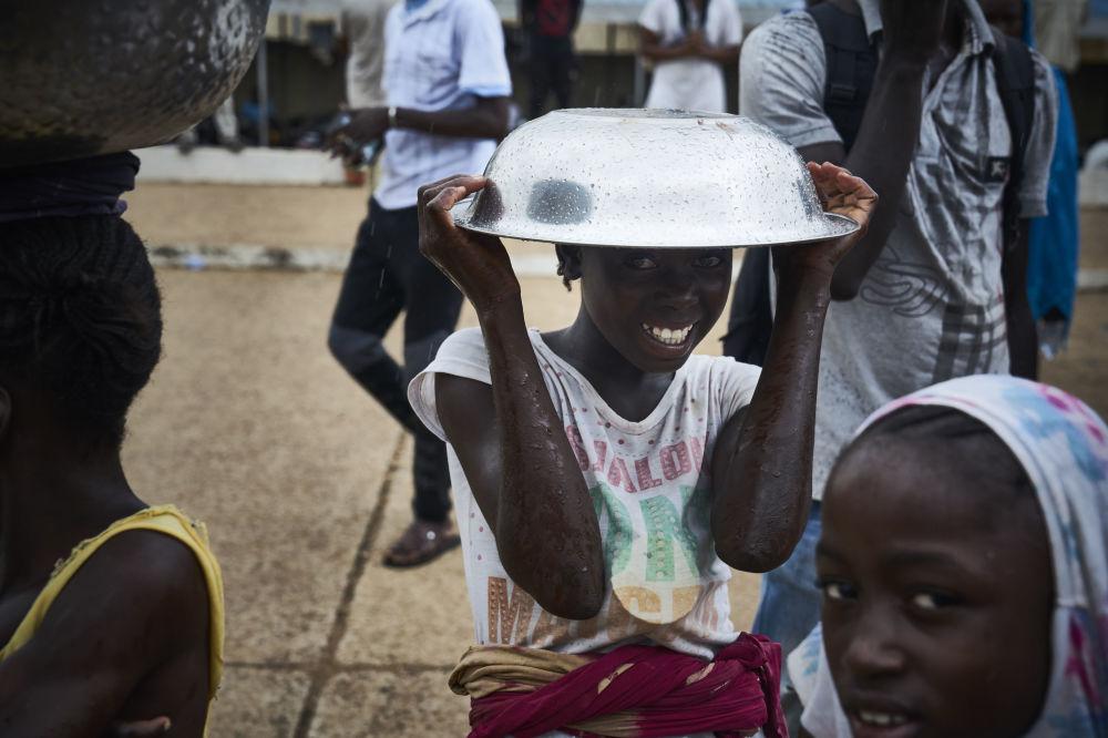 Menina posa com tigela de metal sobre a cabeça, à margem de um protesto contra o presidente maliano em Bamako, em 11 de agosto de 2018
