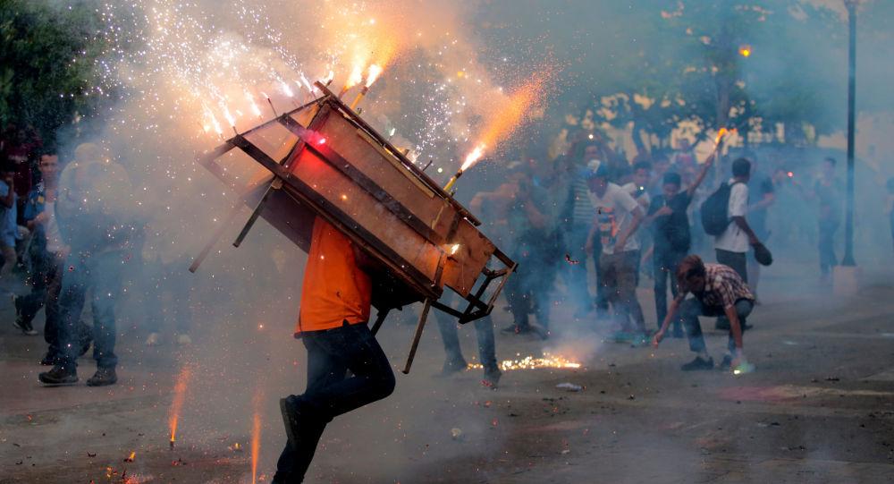 Homem corre com um touro encuetado, uma estrutura que se assemelha a um touro e emite fogos de artifício explodindo, durante um celebração na Nicarágua em 14 de agosto de 2018