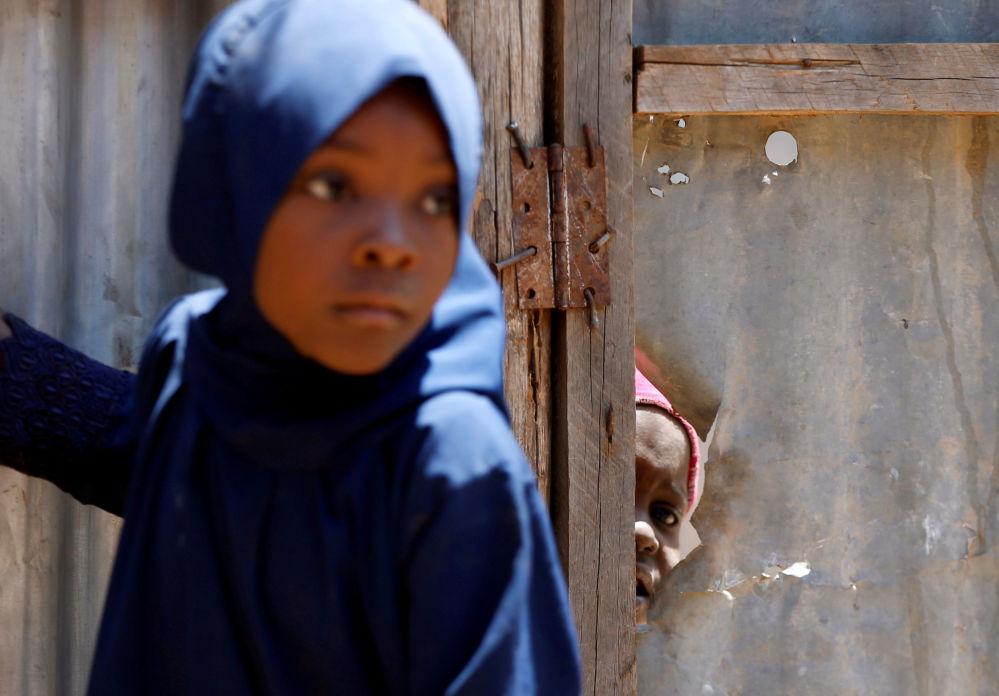 Menina espreita através de um furo no campo de refugiados ao norte do Quênia, em 13 de agosto de 2018