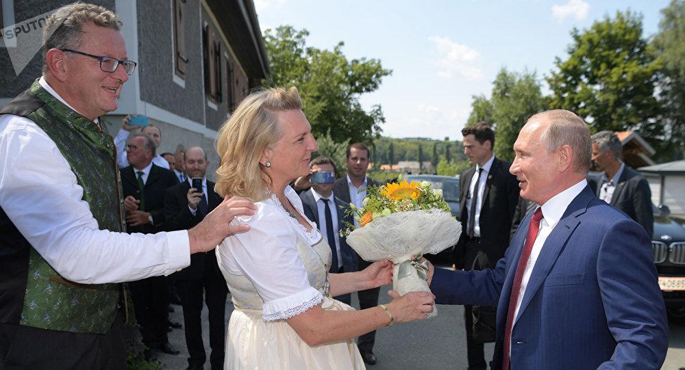Vladimir Putin oferece flores à chanceler da Áustria Karin Kneissl durante seu casamento com o empresário Wolfgang Meilinger