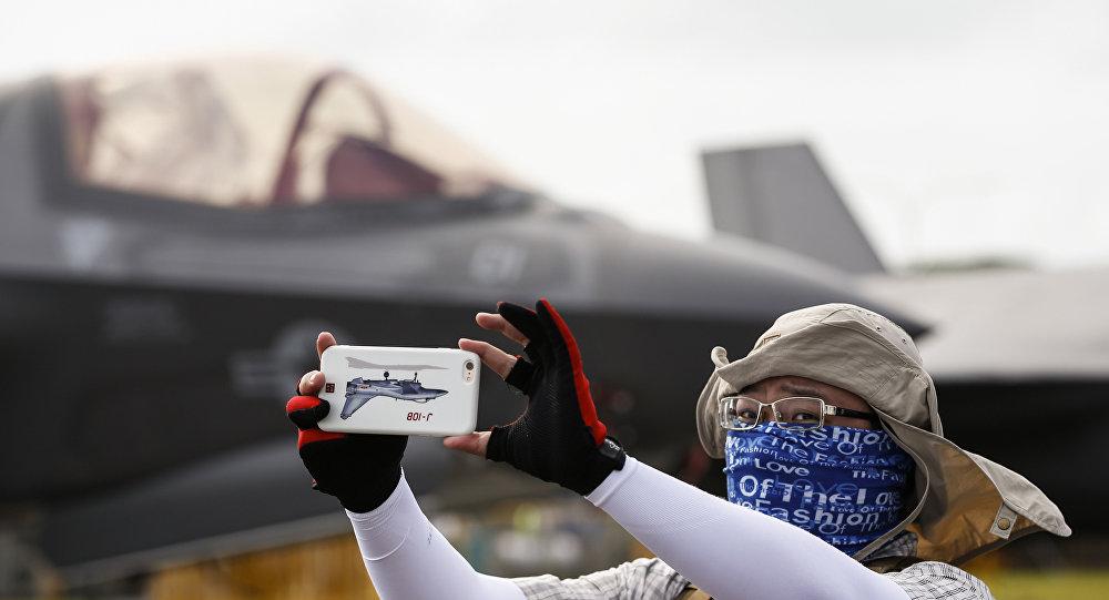 Visitante de um show aéreo em Singapura tirando selfie atrás de um caça F-35B da empresa norte-americana Lockheed Martin