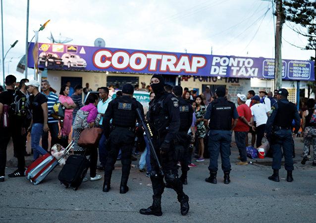 Policiais da tropa de choque conversam com pessoas da Venezuela depois de checar seus passaportes ou carteiras de identidade no controle de fronteira de Pacaraima, Roraima, Brasil