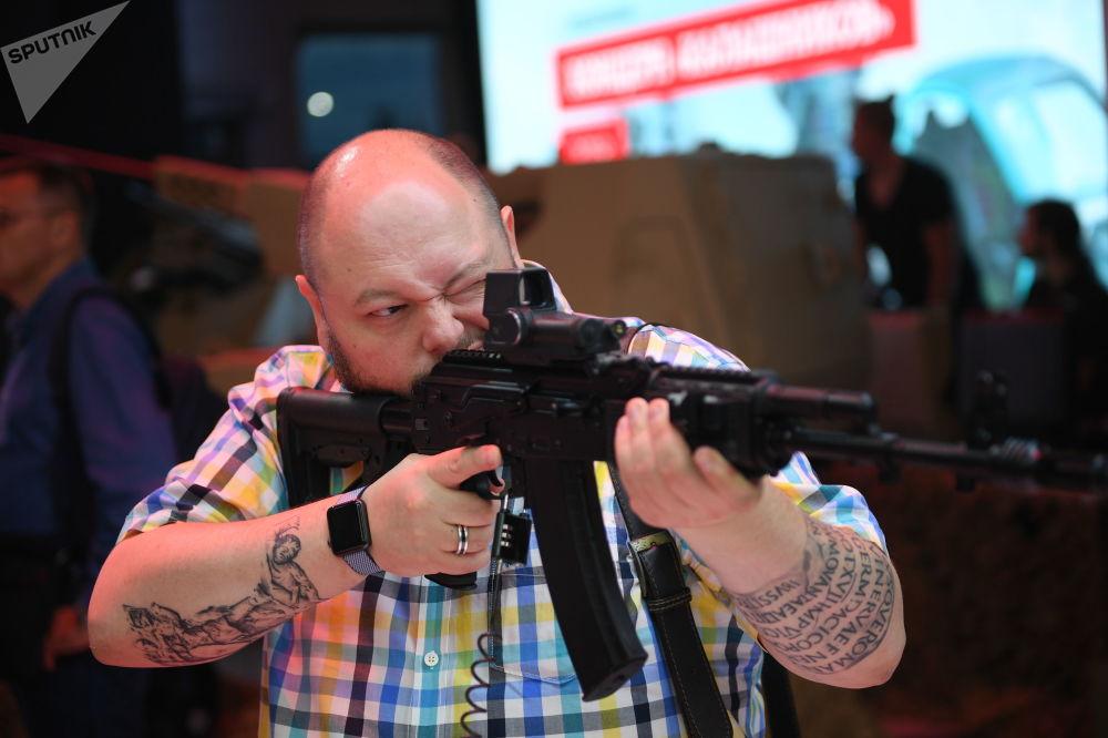 Um visitante segurando o fuzil de assalto Ak-201 do consórcio Kalashnikov no Fórum EXÉRCITO 2018