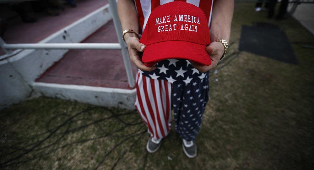 Um homem vestido com roupas de bandeira americana segura o boné Faça a América Grande Novamente.
