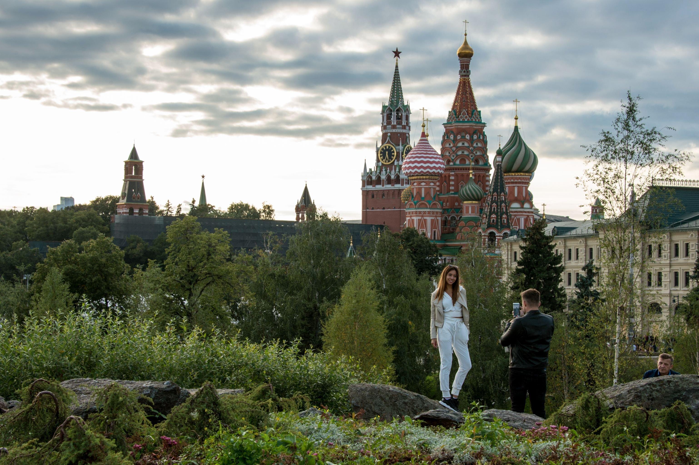 Os visitantes do novo parque de natureza e ambiente Zaryadye em Moscou, tendo como pano de fundo a Torre Spasskaya e a Catedral de São Basílio