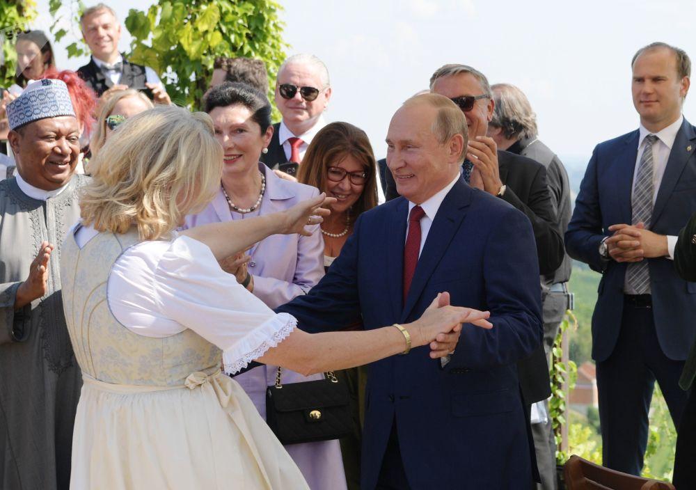 Presidente russo, Vladimir Putin, dança com chanceler austríaca, Karin Kneissl, durante cerimônia de casamento dela
