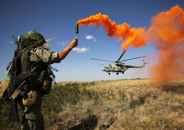 Militar russo participa das manobras táticas do Distrito Militar Sul no polígono de Prudboi, na região de Volgogrado, junto a um helicóptero militar Mi-8