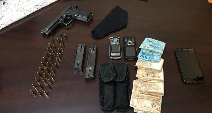 Arma e munição apreendida após operação de busca e apreensão na casa Carlos Moraes.