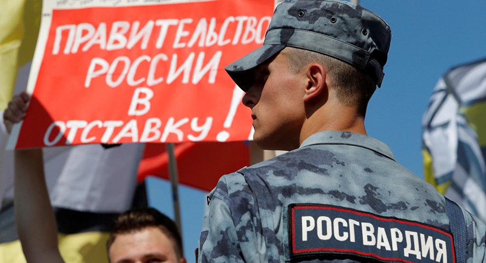 Policial acompanha protesto contra a decisão do governo de aumentar a idade de aposentadoria na Rússia. O cartaz diz Pela reúncia do governo da Rússia!