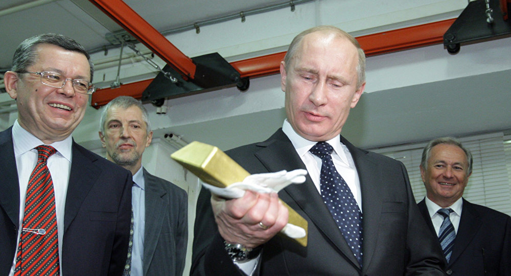 Presidente russo Vladimir Putin segurando uma barra de ouro enquanto visitava o Depositário Central do Banco da Rússia, em 24 de janeiro de 2011