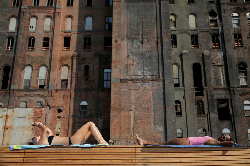 Mulheres tomam banhos de sol no Domino Park em Nova York, nos EUA
