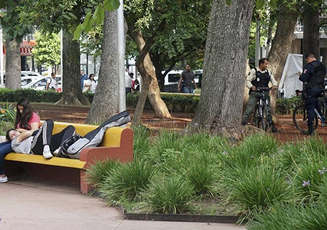 Um casal se acaricia em uma praça pública em Guadalajara, no México. Uma nova lei na cidade instrui os policiais a apenas abordarem casos de sexo em público se houver uma reclamação de terceiros.