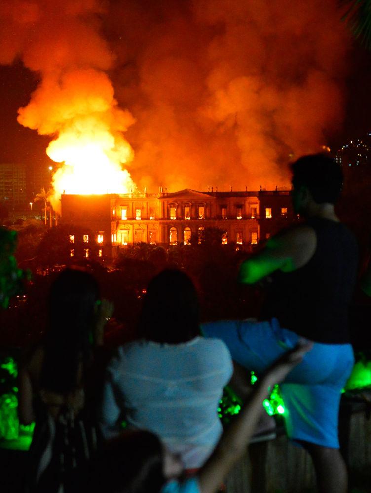 Pessoas observam fogo destruindo o Museu Nacional, no Rio de Janeiro, na noite deste domingo (2)