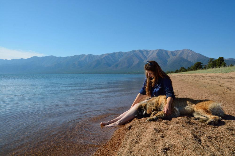 Jovem sentada com seu cachorro na margem do lago Baikal, no sul da Sibéria, em 30 de agosto de 2018