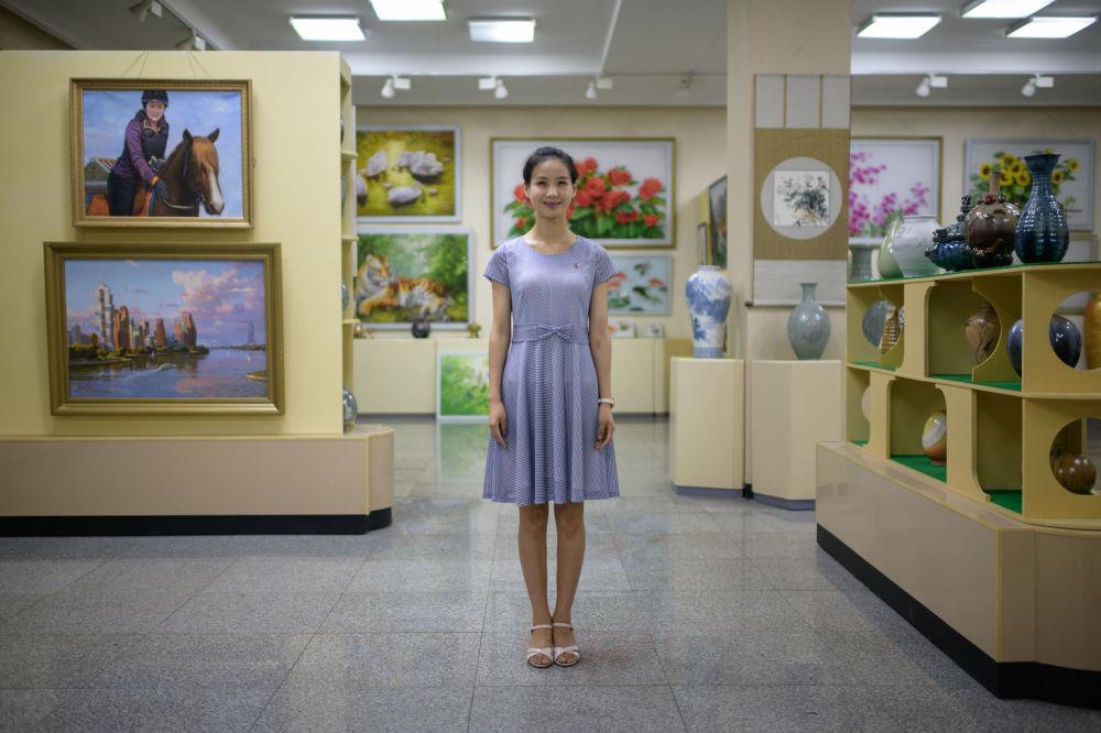 Pak Um Hyang, uma vendedora de 24 anos de idade, no Mansudae Art Studio de Pyongyang, grande complexo de produção em massa de obras de arte e artesanato