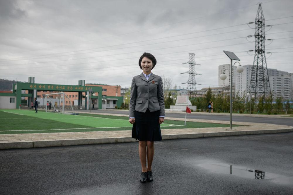 Ma Song Hui, uma estudante e ex-militar do Exército Popular da Coreia do Norte de 26 anos de idade, posa perto da Colégio de Formação de Professores de Pyongyang.